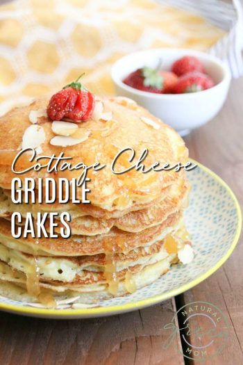 Stack of cottage cheese griddle cakes on a patterned plate with strawberries and slivered almonds
