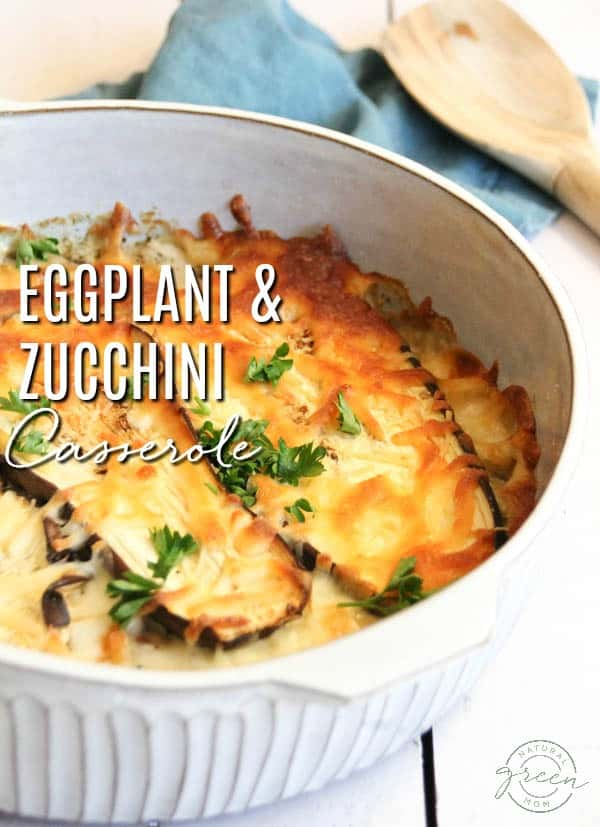 Eggplant and zucchini casserole in a white baking dish with a blue towel and wooden spoon.