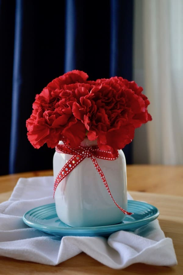 red carnations in a white dollar tree toothbrush holder