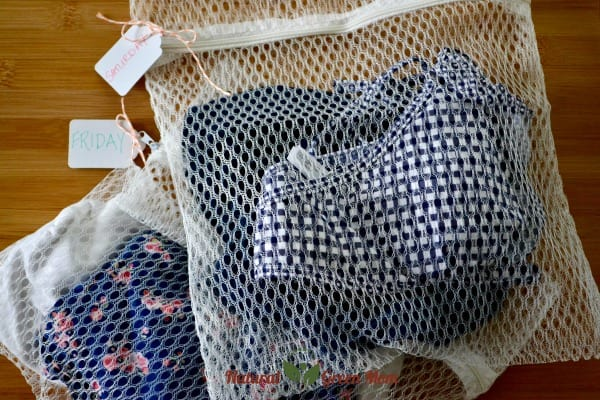 mesh laundry bags with clothes and labeled with days of the week