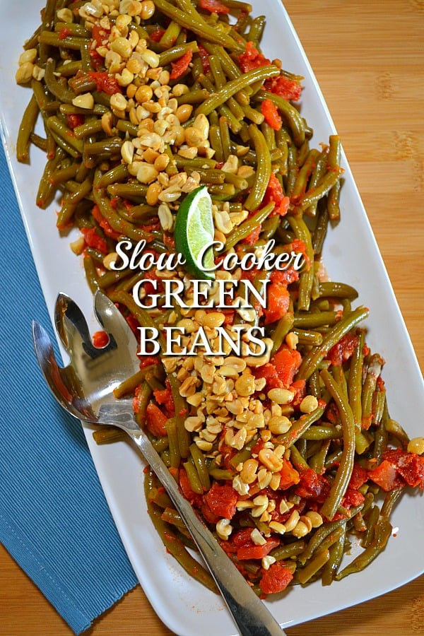 slow cooker green bean recipe with tomatoes, coconut milk, red curry paste and topped with chopped peanuts
