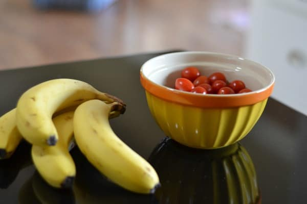 Bunch of bananas and bowl of cherry tomatoes on kitchen counter demonstrating How to Store Produce So It Will Last Longer.