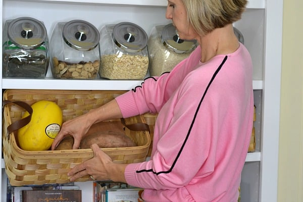 Woman adding potatoes to a storage basket demonstrating How to Store Produce So It Will Last Longer