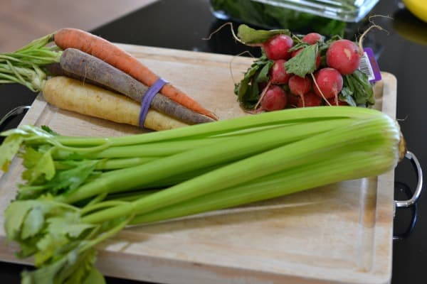 Wood cutting board with bunch of celery, carrots, and radishes on top showing step one to How to Store Produce So It Will Last Longer