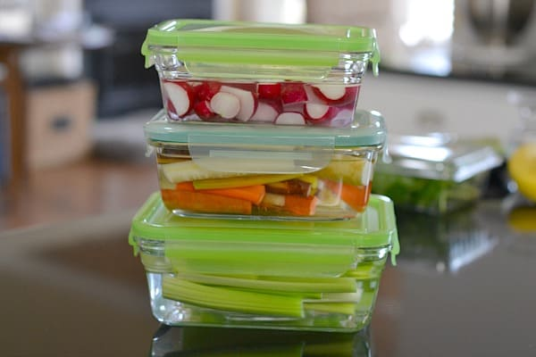 Glass storage containers with sliced radishes, carrots, and celery covered with water demonstrating How to Store Produce So It Will Last Longer