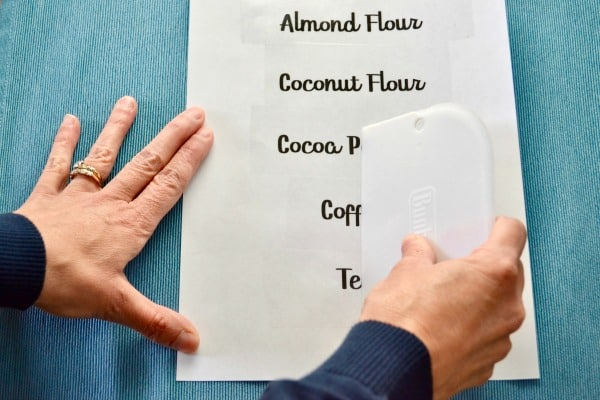 Sheet of pantry labels on a blue background. Hands holding paper steady while scraping and sealing the DIY Clear Pantry Labels.