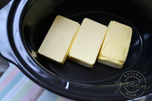 three pounds butter in a black slow cooker showing how to make ghee at home