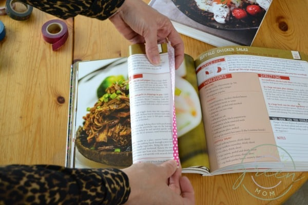 Cookbook on table turned to favorite recipe. Two hands folding pink washi tape over edge of page for easy recipe organizing.