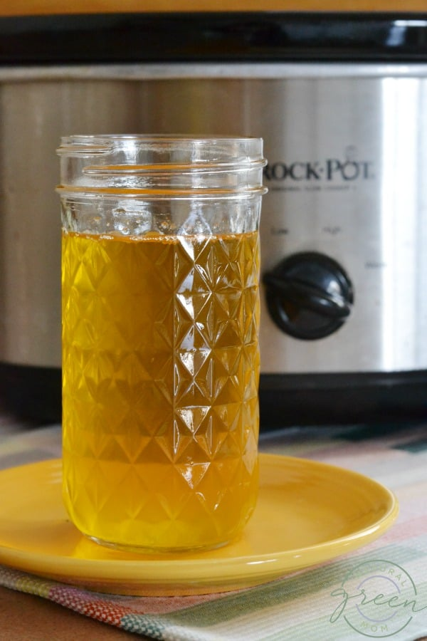 mason jar with ghee on yellow plate in front of slow cooker. Shows how to make ghee at home.