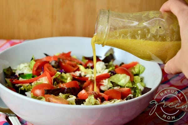 bottle of mustard vinaigrette being poured over a salad of mixed greens and chopped cherry tomatoes