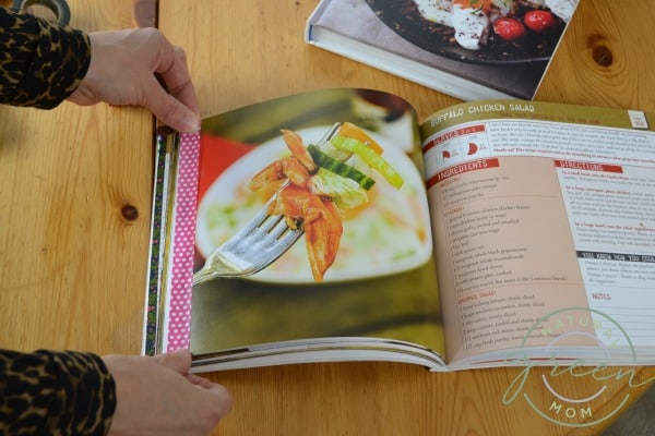 Cookbook on table open to a favorite recipe. Hands holding a stripe of pink washi tape along page edge for recipe organizing.