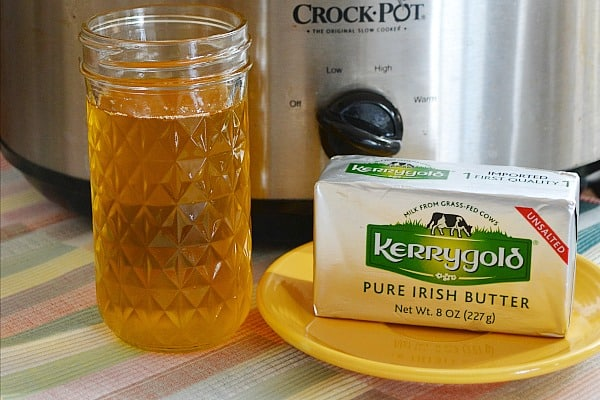 mason jar with ghee, small yellow plate with kerrygold unsalted butter, slow cooker in background used to make ghee at home