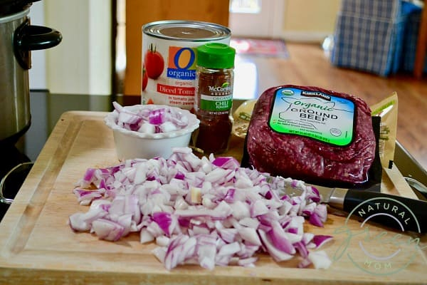 Chili for hot dogs ingredients including chopped red onion, a jar of chili powder, a can of crushed tomatoes and a pound of ground beef.