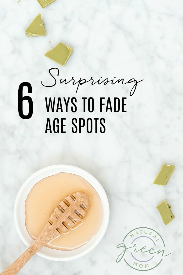 White marble background with white bowl containing honey and honey stick and green soap pieces with title 6 Surprising Ways to Fade Age Spots Naturally