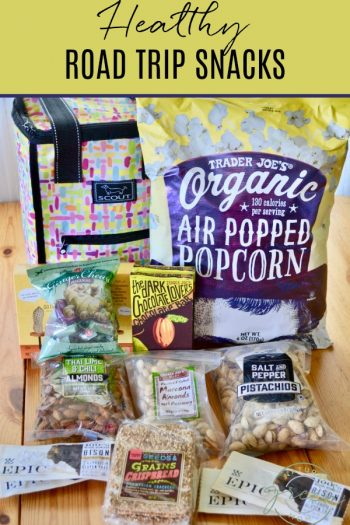 An assortment of healthy road trip snacks including organic air popped popcorn, dark chocolate bars, nuts, and jerky.