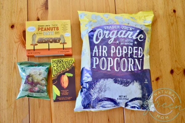 Healthy road trip snacks on a table including air popped popcorn, dark chocolate, granola bars, and gin gin chews