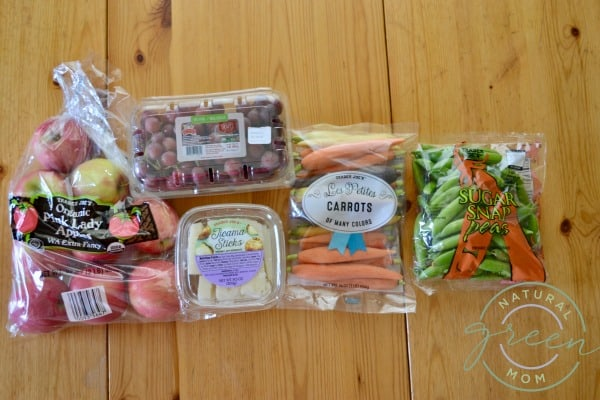 Healthy road trip snacks including apples, grapes, jicama, carrots, and sugar snap peas