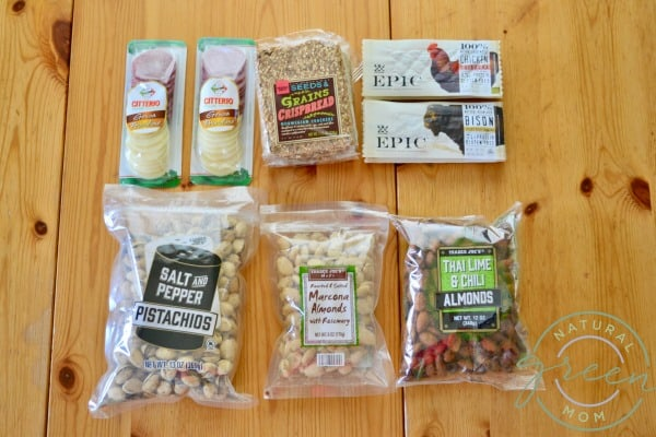 Healthy road trip snacks including pistachios, almonds, salami and cheese packs, and jerky