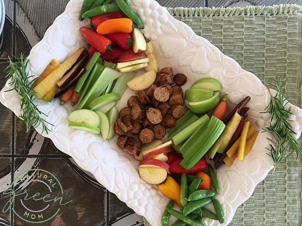 white platter with sausage, fruits and vegetables representing a picnic to eat cheap while on vacation