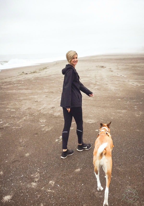 Woman dressed in workout attire with dog walking on beach while getting her 10,000 steps a day.