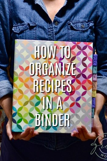Woman in blue shirt holding binder showing how to organize recipes in a binder.