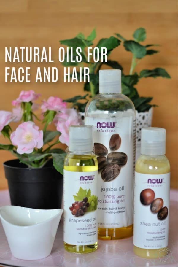 Natural oils for face and hair including jojoba oil, grapeseed oil, and shea butter oil on tray with flowers and plant.