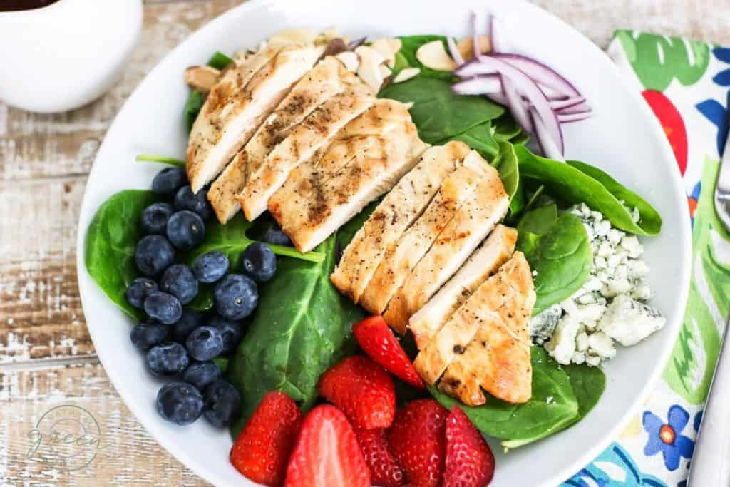 Grilled chicken on bed of spinach with blueberries, strawberries, red onion, and blue cheese.