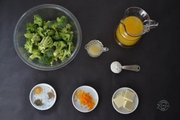 Steamed broccoli with the ingredients for orange sauce laid out.