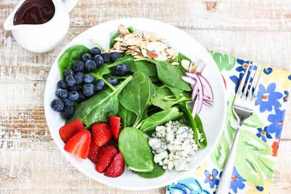 Restaurant worthy grilled chicken salad with bed of spinach, blueberries, strawberries, blue cheese, red onion, and slivered almonds.