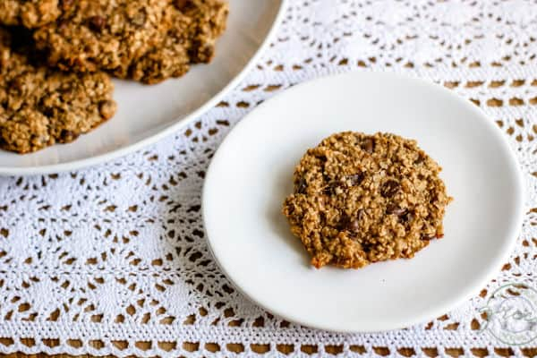 Single 3 ingredient chocolate chip cookie on a white plate on a white lace tablecloth