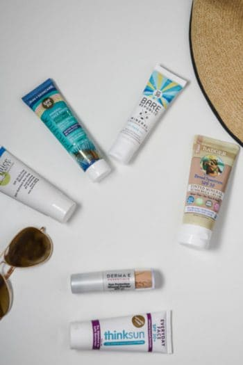 Round up of the best non toxic face sunscreens on a white background with a floppy hat and sunglasses