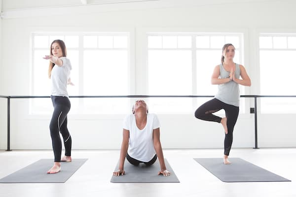 3 women each demonstrating a different yoga for toning pose