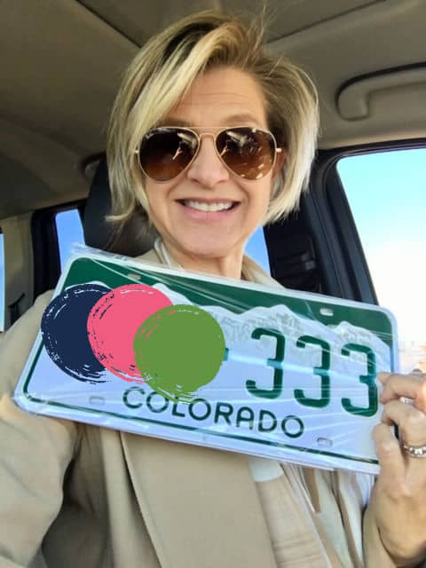 Woman holding license plate with triple digit 3