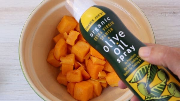 Trader Joe's olive oil spray bottle held over a bowl of butternut squash