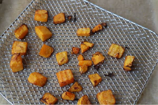 Air fried pieces of butternut squash on a baking tray